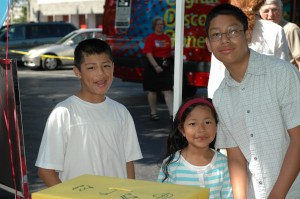 Asian brothers smiling with their younger sister near ABC Library vehicle.