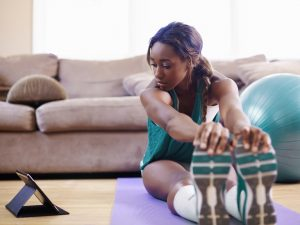 Woman stretching on yoga mat in her living room while watching fitness video on tablet