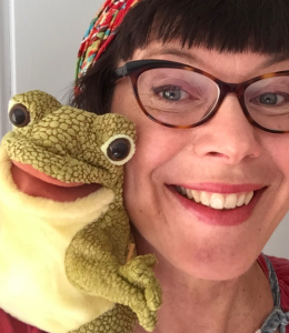 Woman holding frog plush next to her face and smiling