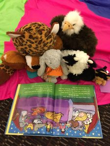 Stuffed animals reading a picture book