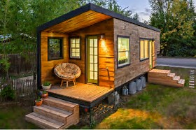 Cozy tiny house with a welcoming porch and lights on inside casting a warm glow in the evening