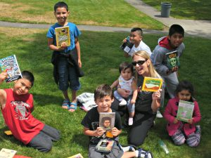 Children and adult holding books up on a grassy lawn