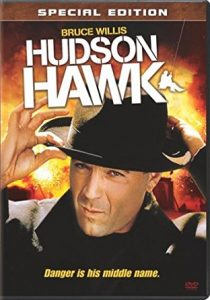 "A movie poster: Actor Bruce Willis fixing a black fedora on his head. A tagline reads ""Danger is his middle name."""