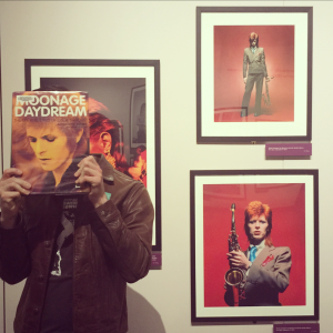 Young man holds book of David Bowie photography over face, in museum gallery space
