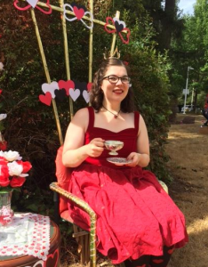 Peggy dressed as the Queen of Hearts from Alice in Wonderland, sitting in a fancy chair sipping tea