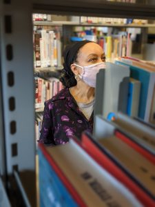 Library staff member browsing books in the library. The staff member is wearing a face mask that covers their nose and mouth.