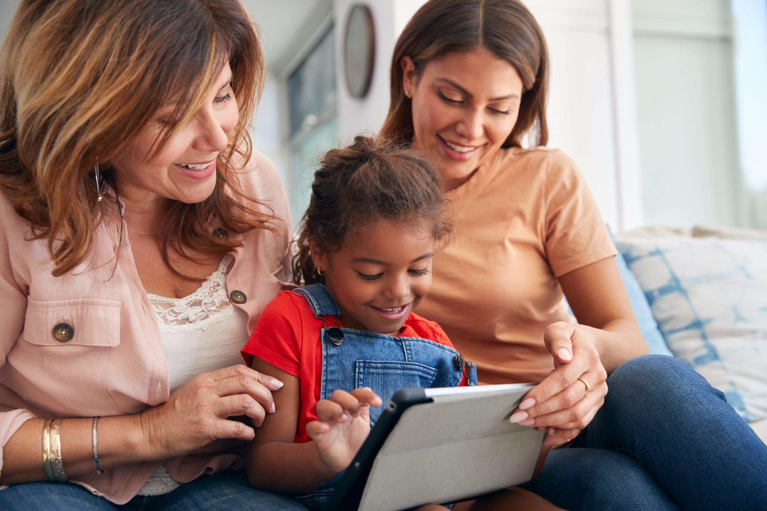 Multi-Generation Female Hispanic Family Sitting On Sofa At Home Using Digital Tablet