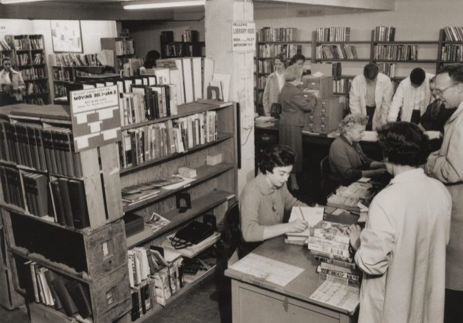 People getting their books checked out by staff at the Bellevue library (vintage)