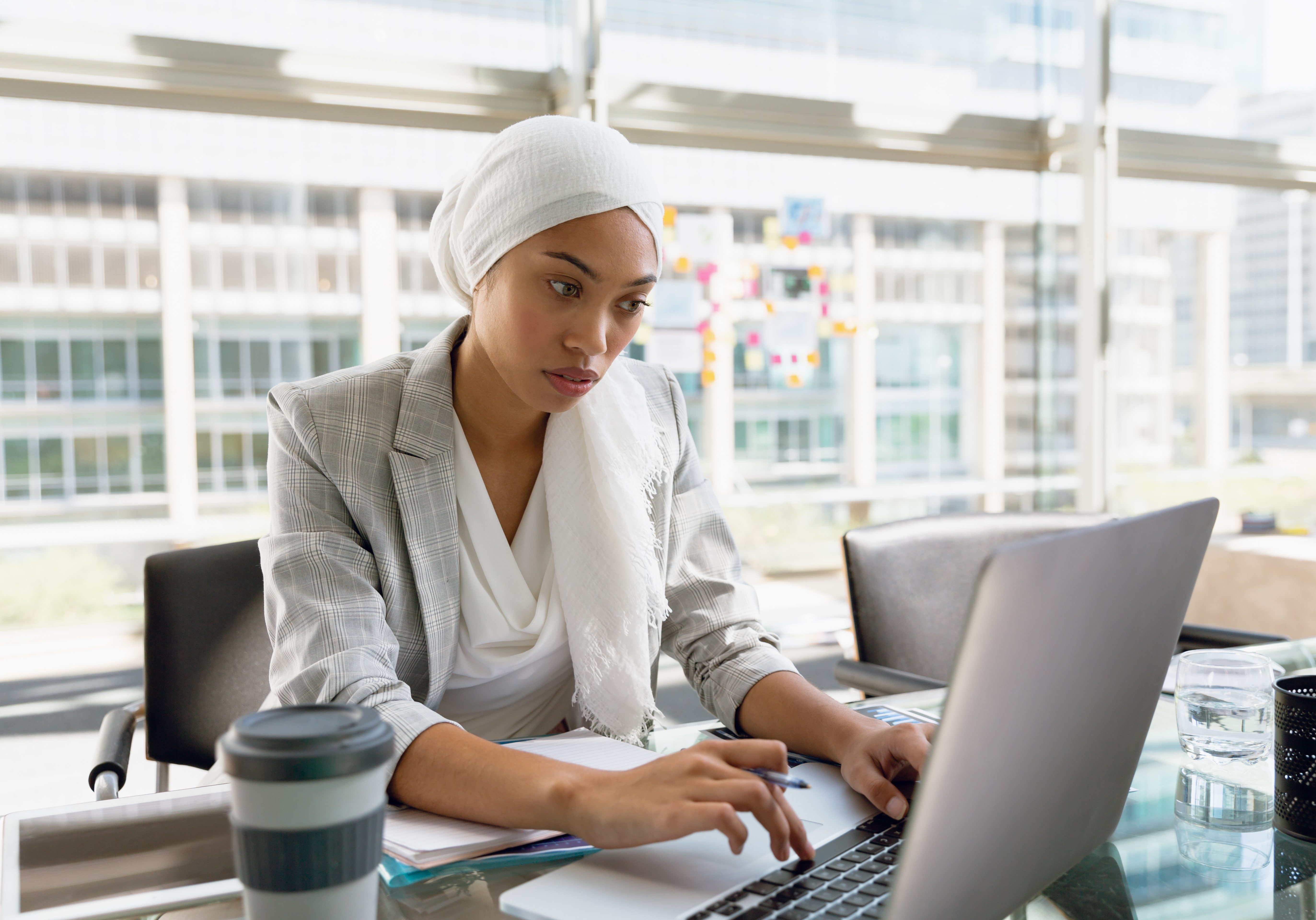 Front view of businesswoman in hijab working on laptop at desk in a modern office. Modern corporate start up new business concept with entrepreneur working hard