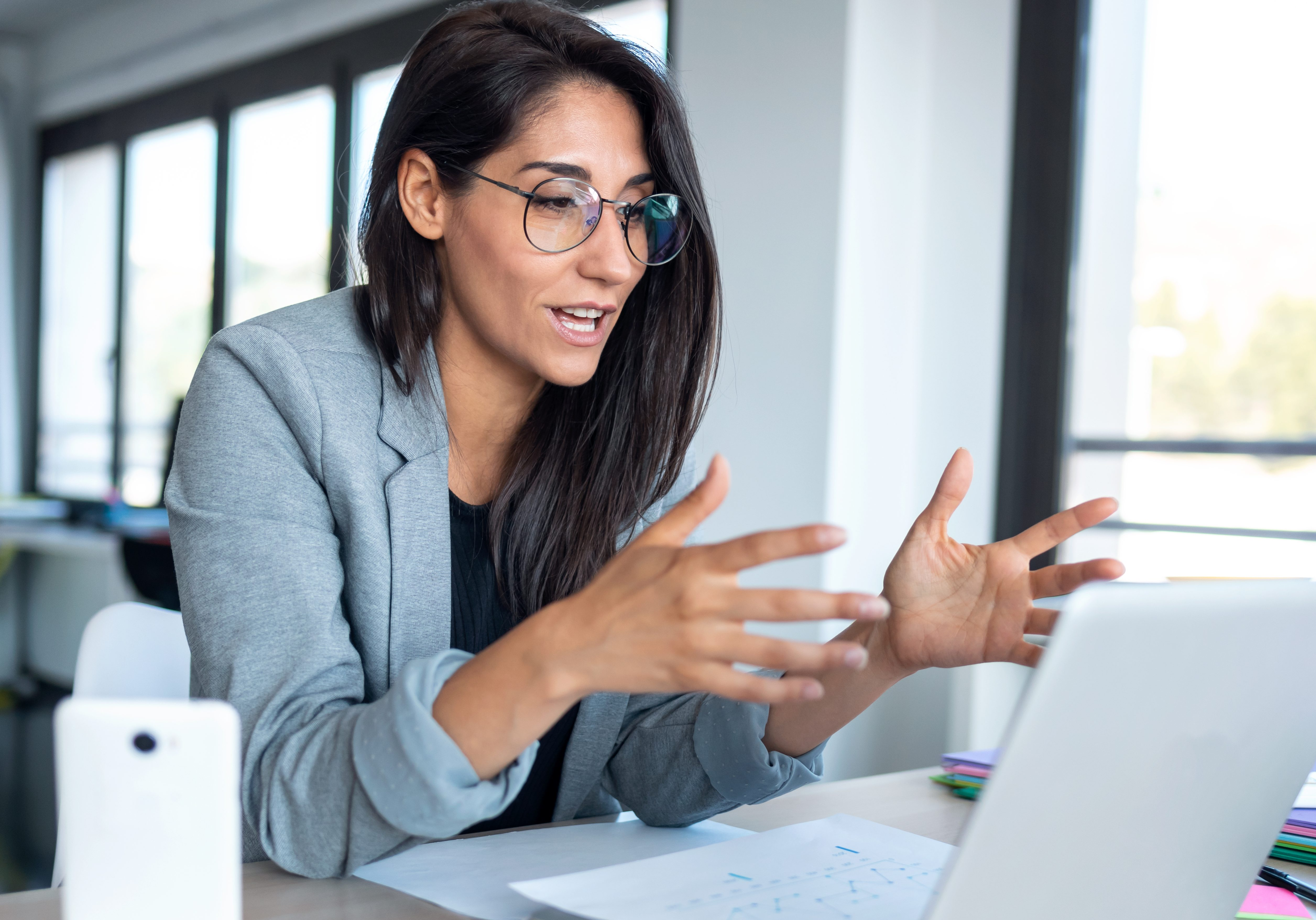 Confident business woman looking and speaking through the webcam