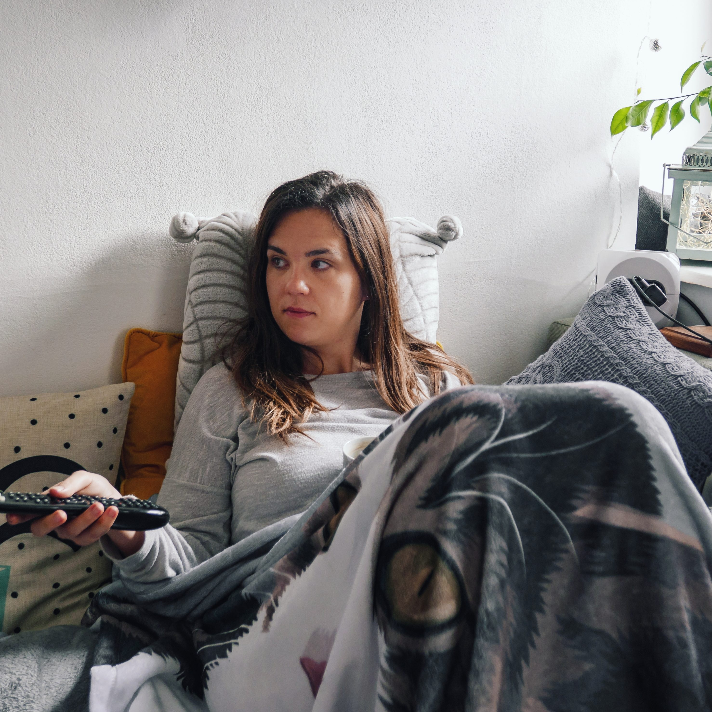 young-woman-watching-tv-woman-on-a-couch-sofa-cozy-bundled-up-blanket-flat-apartment-person-rent_t20_vRmNeG